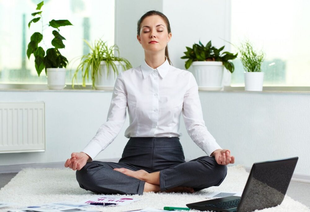 office-woman-meditating-near-laptop-with-plants-in-the-background-1024x682